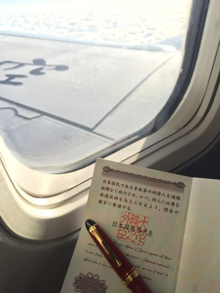 飛行機の窓から雲の下を眺める