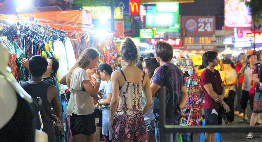 タイのバンコクのカオサン通りで買い物をする若い女性の写真