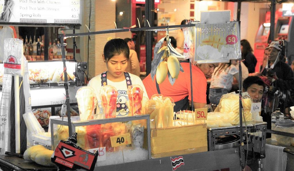 タイのバンコクのカオサン通りで果物を売る女性の写真
