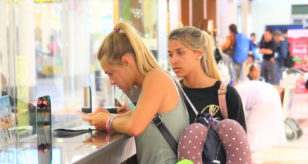 海外旅行はベトナムへ。ホーチミン空港で両替をする観光客の白人美女たちの写真