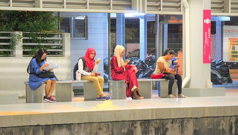 マレーシアの電車の駅のホームにくつろぐ人たち