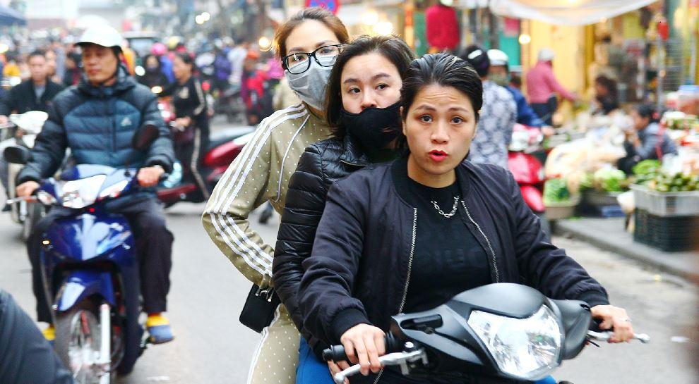 ハノイ旧市街をバイクで三人乗りで走る女性|ベトナム旅行