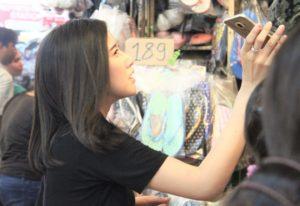バンコクのチャトゥチャック市場で価格交渉する若いタイ人の女性 タイ観光