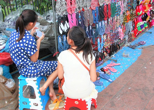 バンコクのチャトゥチャックマーケット前の露店で働く少女たち