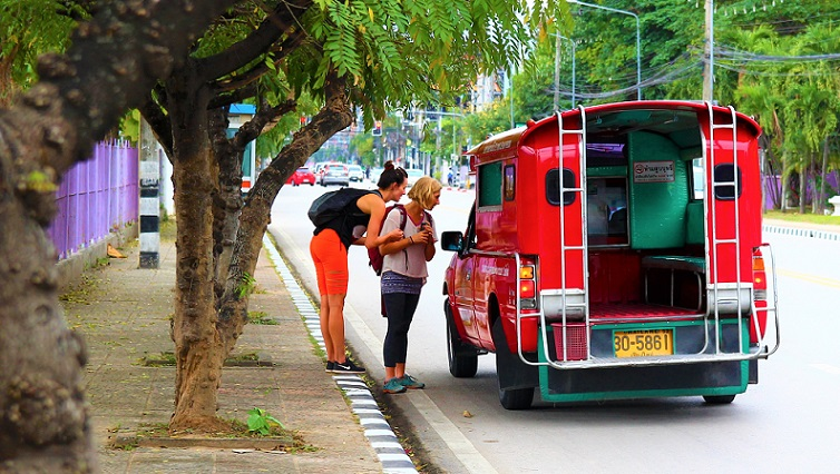 タイのチェンマイ大学前の大通りでソンテウに乗るバックパッカーの白人女性たちの写真