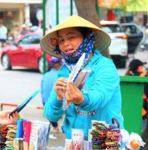 ベトナムの観光地で歩いて行商をするベトナム人の女性