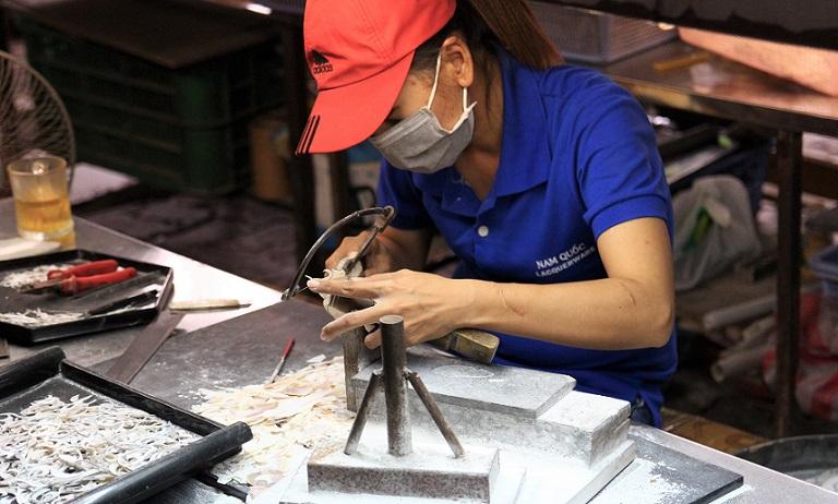 ホーチミンの螺鈿細工の工場で糸ノコギリで貝を加工する職人の写真|ベトナム旅行