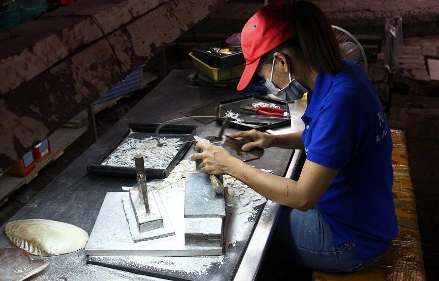 ホーチミンの伝統工芸品|螺鈿細工の工場で小刀で貝を切る職人の写真|ベトナム旅行