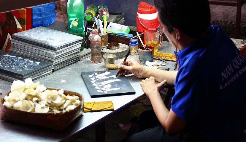 螺鈿細工の工場で木材に卵の殻を埋め込んでいく職人の写真|ベトナム旅行