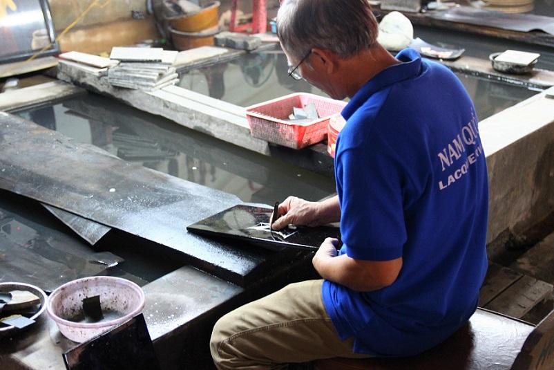 ホーチミンの螺鈿細工の工場|水で木材と貝の表面を研磨する職人の写真|ベトナム旅行