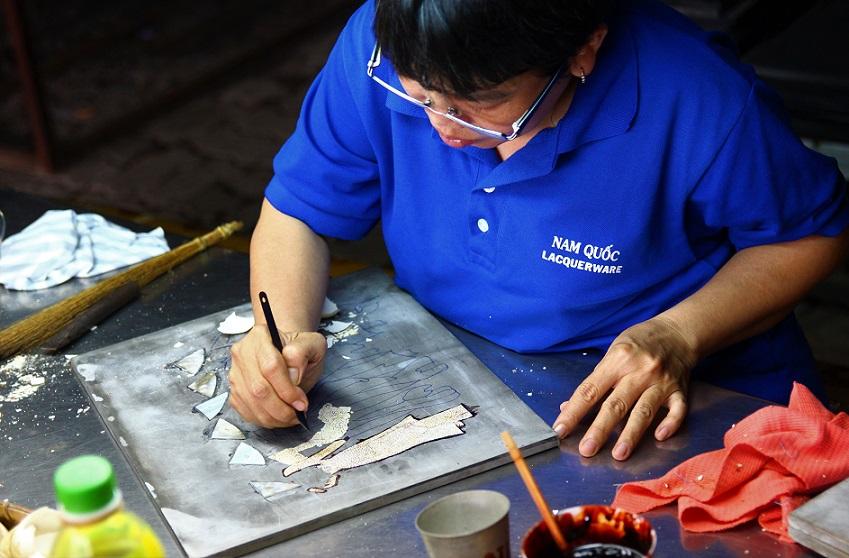 ホーチミン螺鈿細工の工場で型に合わせて木材を加工する職人の写真|ベトナム旅行