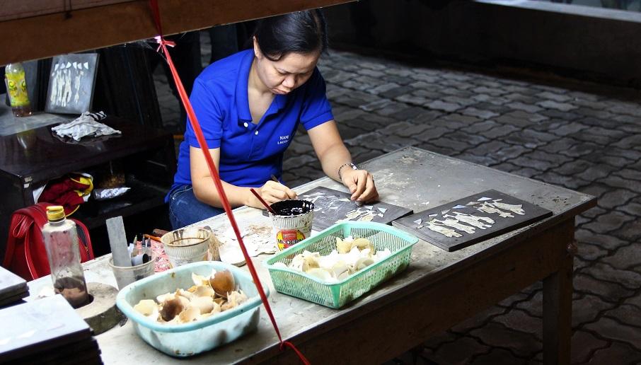 ホーチミンの螺鈿細工の工場でくり抜いた木に貝を埋め込んでいく職人の写真|ベトナム旅行