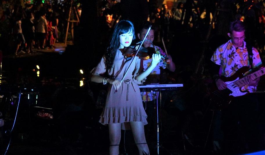 ハノイのホアンキエム湖のほとりでヴァイイオリンの生演奏をする女性【ベトナム旅行】