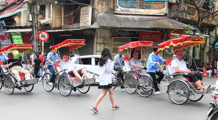 ハノイの旧市街を走るシクロをよけて歩く女性【ベトナム旅行】