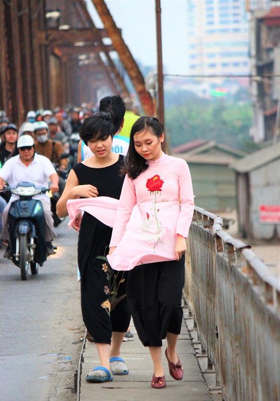 ハノイのお勧めスポット、ロンビエン橋の横の歩道を歩くアオザイを着た女性【ベトナム旅行】