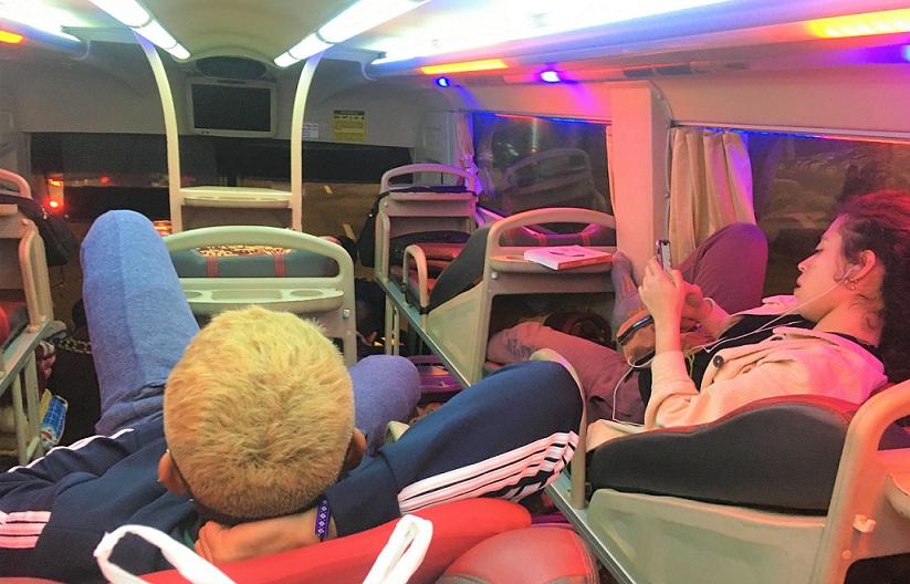 ハノイからフエ・ホイアン方面行のバスの車内でくつろぐベトナム人の若いカップルの写真。