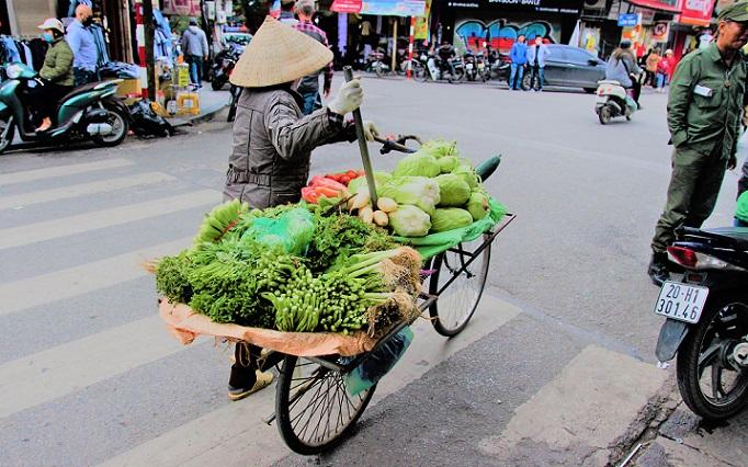 ハノイの道路で野菜を昔ながらの行商をする老婆の写真