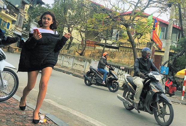 ハノイの街を歩く美女とバイク、ベトナムの活気と喧騒が伝わってくる。