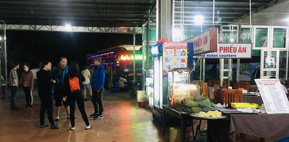 フエ行きのバスが深夜に立ち寄った休憩所で、食事をしビールを買うアメリカ人観光客たちの写真。