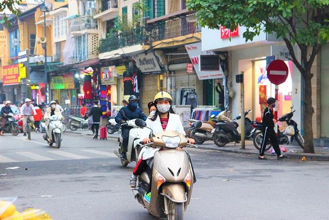 ベトナムのハノイを日本製のホンダのバイクで走るOL女性の写真