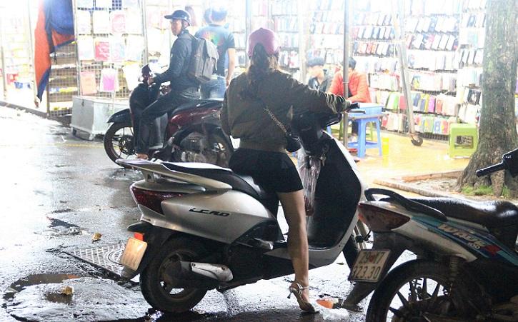 ハノイ旧市街の定番お買い物スポットのドンスアン市場で買い物を終えてバイクで買える女性の写真|ベトナム旅行
