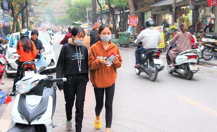 ハノイのハンチエウ通りとグエンシエウ通りの交差点を歩くベトナムの少女達の写真