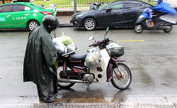 フエで買い物をした荷物をバイクに載せるベトナム男性