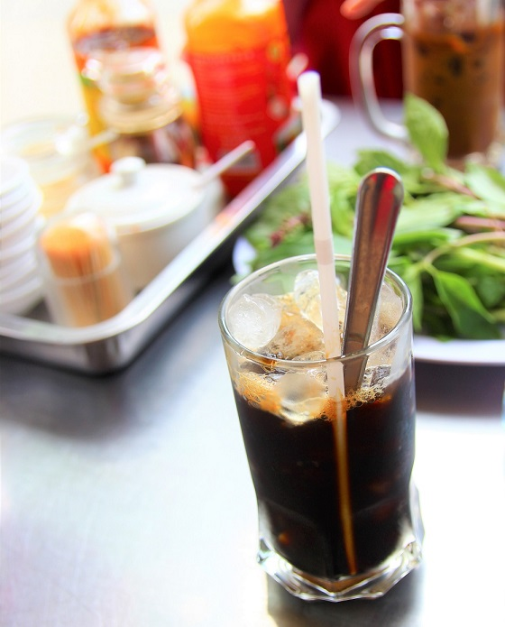 フォークインのテーブルに置かれた調味料と野菜とベトナムアイスコーヒーの写真