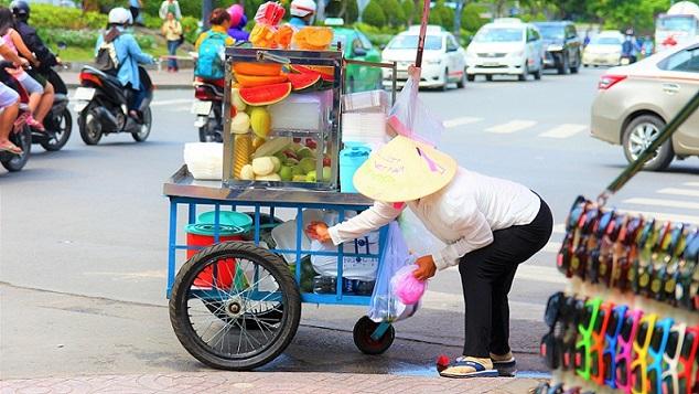 ホーチミンのフォークインの前で果物を売るベトナム人女性の写真