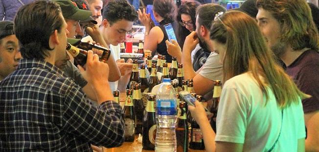 ベトナムの夜の街のタヒエン通りでビールを飲む外国の若者たちの写真