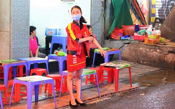 ベトナムの夜の街でビアガールの制服を着て働くハノイ女性の写真
