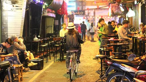 ハノイの夜の街で仕事を終えて帰るベトナムの女性の写真