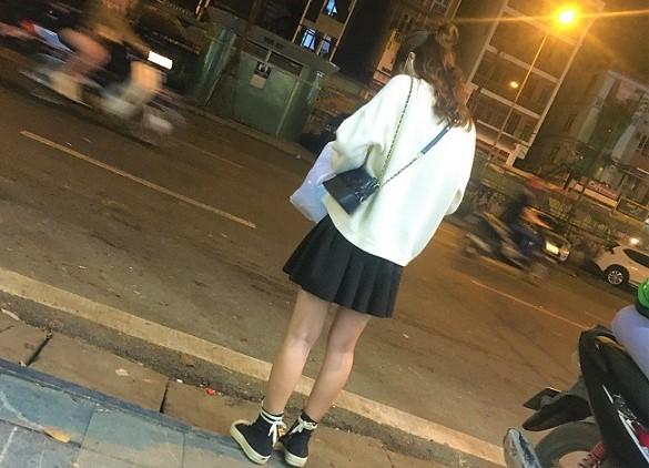 ハノイの夜の街でアルバイトを終えて帰宅するベトナムの女子高生の写真