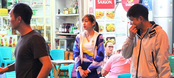 シンハービールの制服を着てタヒエン通りのビアストリートで客引きをするベトナムの少女の写真
