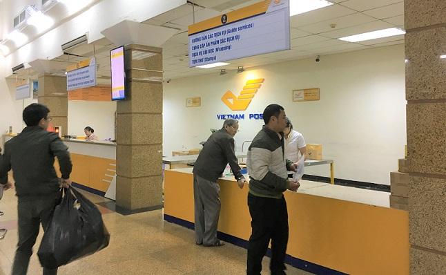 ハノイ郵便局の内部のカウンターと利用者たちの写真