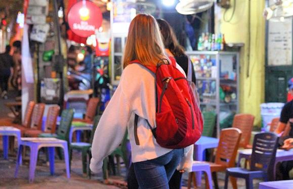 ベトナムのタヒエン通りを歩く女性バックパッカーの写真