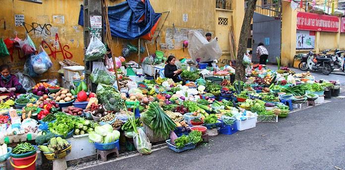 ハノイ旧市街のドンスアン市場の場外で野菜を売る商人たちと並べられた大量の商品の写真