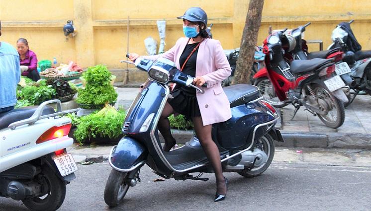 ハノイ旧市街のドンスアン市場の場外売り場で野菜を買って帰る、バイクに乗ったベトナムの若い女性の写真。