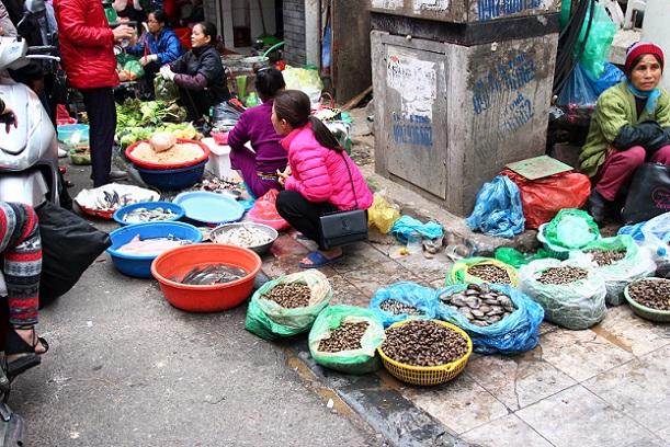 ドンスアン市場の場外売り場で貝や魚を売る女たちの写真