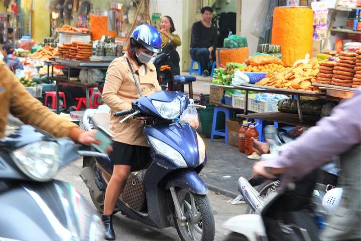 ハノイ旧市街のドンスアン市場で夕食のおかずを買う若いベトナム人女性の写真