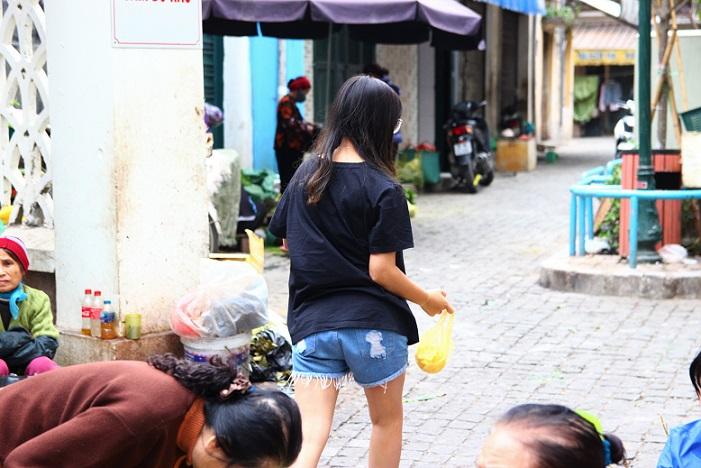 ドンスアン市場の場外売り場で夕食のおかずを買って帰るベトナム人の女子高生の写真