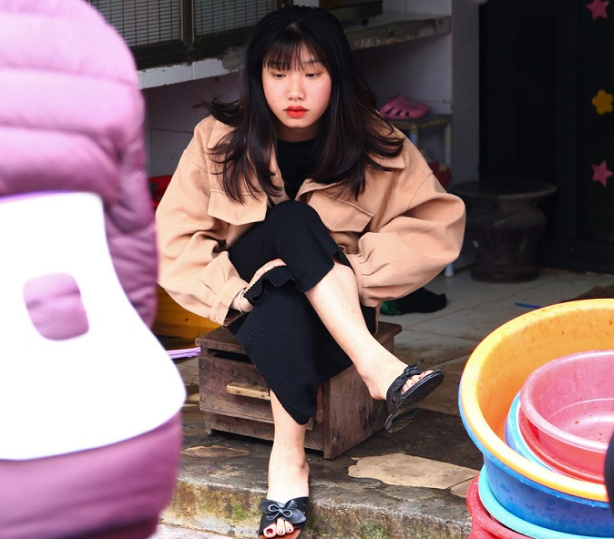 ドンスアン市場の裏のカオタン通りで店番をするベトナム人女子高生の写真