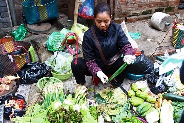 ハノイ旧市街のドンスアン市場裏のカオタン通りで野菜を加工しながら販売するベトナム人女性の写真