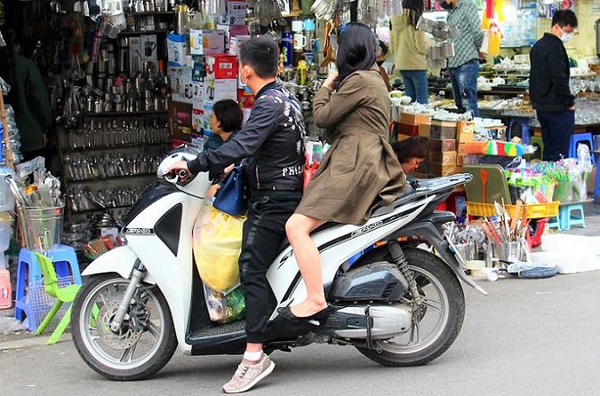ドンスアン市場の横の雑貨と金物を売る店で、バイクに乗ったまま買い物する若いベトナム人カップルの写真。