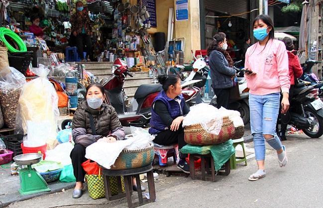 ハノイ旧市街のドンスアン市場横のハンコアイ通りを通るベトナム人女性の写真
