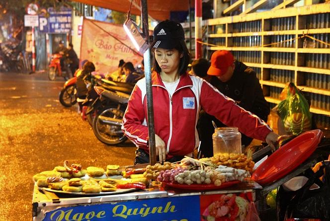 夜にハノイ旧市街のドンスアン市場の横で串揚げの屋台を開く女性の写真