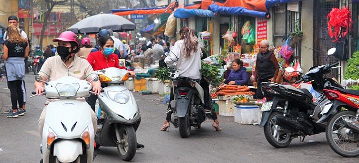 ハノイ旧市街ドンスアン市場の場外売り場を訪れる買い物客たちの写真