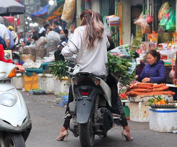 ハノイ旧市街ドンスアン市場の場外売り場で大量の野菜を買うバイクの若い女性の写真