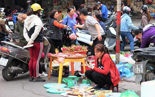 ドンスアン市場の場外でドラゴンフルーツなどの果物を売っている家族の写真