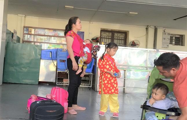 ザーラムバスターミナルでバスの出発を待つアオザイ少女と家族の写真
